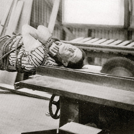 Image of a tied up Harry Houdini on a running table saw. Buzz. Buzz.